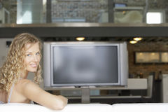 Young Woman In Living Room With Plasma Television In Background Royalty Free Stock Photos