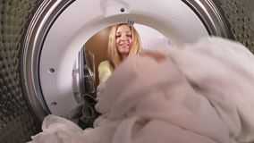 Young woman loading the clothes to washing machine. View from the inside of washing machine stock video footage