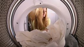 Young woman loading the the clothes to washing machine. View from the inside of washing machine. Slow motion stock footage