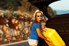 Young woman loading luggage into the back of car. Parked alongside the road Royalty Free Stock Photo
