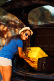 Young woman loading luggage into the back of car. Parked alongside the road Stock Photo