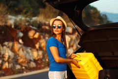 Young woman loading luggage into the back of car. Parked alongside the road Stock Photos