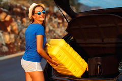 Young woman loading luggage into the back of car. Parked alongside the road Stock Photography