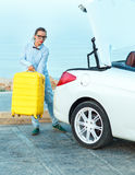 Young woman loading luggage into the back of convertible car. Parked alongside the road Royalty Free Stock Photo