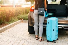 Young woman loading two blue plastic suitcases to car trunk. stock image