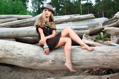 Young woman on logs in the forest Stock Photography