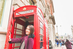 Young woman in London in front of a typical red phone booth Royalty Free Stock Photography