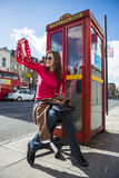 Young woman with london phone booth at back. Low angle shot of fashionable young woman waving by street with red phone booth behind her Royalty Free Stock Image