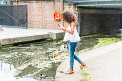 Young woman in London playing with augmented reality application Royalty Free Stock Images