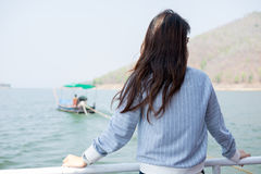 Young woman lone moment standing viewing scenery on boat. front Royalty Free Stock Photos