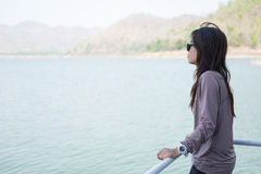Young woman lone moment standing viewing scenery on boat. front Stock Photo