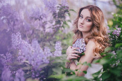Young woman with long beautiful hair in a chiffon dress posing with lilac Royalty Free Stock Photos