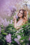 Young woman with long beautiful hair in a chiffon dress posing with lilac Royalty Free Stock Image