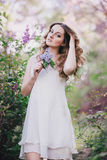 Young woman with long beautiful hair in a chiffon dress posing with lilac Royalty Free Stock Images