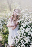 Young woman with long beautiful hair in a chiffon dress posing with lilacin garden with white flowers Royalty Free Stock Images