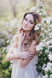 Young woman with long beautiful hair in a chiffon dress posing with lilacin garden with white flowers Stock Image