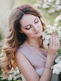 Young woman with long beautiful hair in a chiffon dress posing with lilacin garden with white flowers Royalty Free Stock Photo