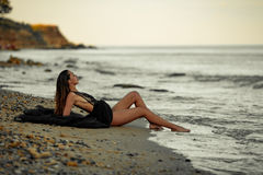 Young woman in long black dress sits on sand beach by the sea. Stock Images