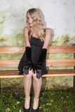 Young woman with long blond hair and elegant mini dress sitting on a bench Stock Photos