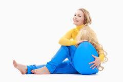 Young Woman with Long Blond Hair and Large Blue Egg. Stock Photos