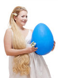 Young Woman with Long Blond Hair and Large Blue Egg. Stock Photo
