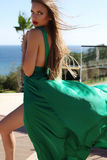Young woman with long blond hair in luxurious green silk dress Royalty Free Stock Photography