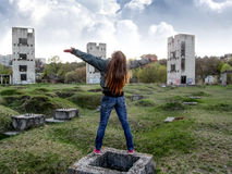 A young woman with long blond hair is standing with hands spread to the sky. In the background, a terrible sky and three unfinished high-rise buildings Royalty Free Stock Photo