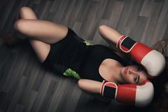 Young woman with long blonde hair and closed eyes, dressed in fitness clothing and wearing red boxing gloves, lying on dark floor royalty free stock images