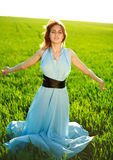 A young woman in a long blue dress enjoying nature Royalty Free Stock Image