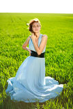 A young woman in a long blue dress enjoying a sunny day Stock Images
