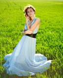 A young woman in a long blue dress enjoying a sunny day Royalty Free Stock Photos