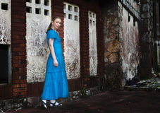 The young woman in a long blue dress stands near the old destroyed stone wall of the building Royalty Free Stock Photo