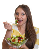 Young woman with long brown hair eating salad Stock Images