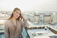Woman standing in bathrobe on terrace outdoor with city scape. Young woman with long brown hair looks happily at camera, dressed in comfortable bathrobe stock image