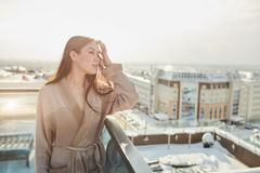 Woman standing in bathrobe on terrace outdoor with city scape stock photos