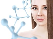 Young woman with long brown hair near big molecule chain. Young woman with long brown hair near big white molecule chain. Over white background. Innovation Royalty Free Stock Image