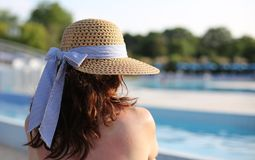 Pretty woman with a big straw hat and she relaxes in the exclusi stock photos