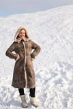 Young woman in long coat standing on snowy area. Young beauty woman in long coat standing on snowy area and smiling, winter day Stock Photo
