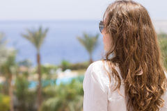 Young woman with long curly hair looks at seaside Royalty Free Stock Images