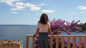 Young woman with long curly hair standing on the terrace by the sea. Near a flowering bush and in the distance a. Beautiful sea view stock video