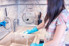 Young woman with long dark hair cleans a granite sink in the kitchen royalty free stock photo