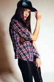 Young woman with long dark hair wears casual plaid shirt and cap Royalty Free Stock Images