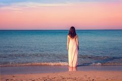 Young woman in a long dress on the beach royalty free stock images