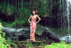 Young woman in a long dress near a waterfall Royalty Free Stock Photography