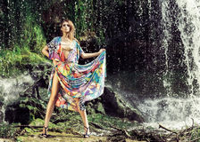 Young woman in a long dress near a waterfall Stock Image