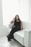 Young woman in long dress relaxing on white couch next to window Royalty Free Stock Photos