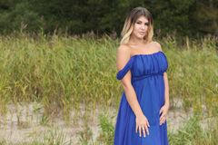 Woman in long dress sits on sand beach Royalty Free Stock Photography