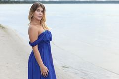 Woman in long dress sits on sand beach Stock Images