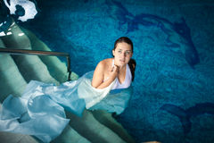 Young woman in long dress walking down the stairs at swimming po Royalty Free Stock Image
