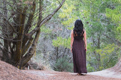 Young woman in long dress walks barefoot in forest Stock Image